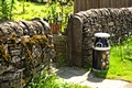 >Hand Painted Milk Churn Beside Gateway by Rod Johnson