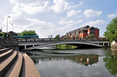 A view of the River Derwent and Exeter Bridge at Derby. There are tall buildings in the background. Link to Bridges Gallery.